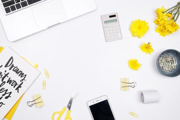 ノートパソコン、ノートブック、白い背景に黄色の花と女性の作業スペース。