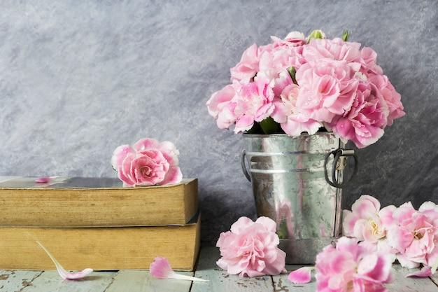亜鉛バケツのピンクのカーネーションの花とテーブルの木の古い本