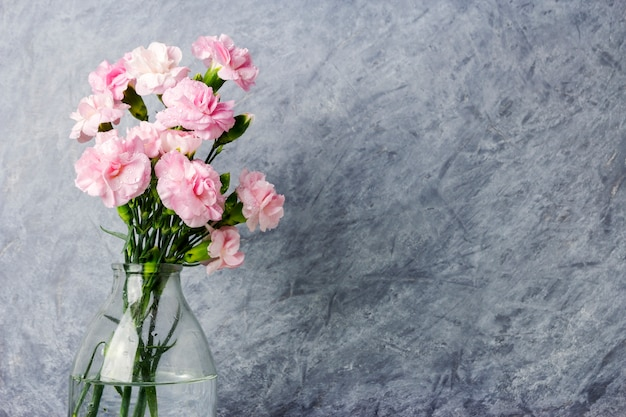 透明な瓶のピンクのカーネーションの花