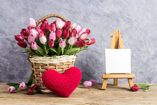 赤い心とイーゼルペインティングの空白のキャンバスフレームと木のバスケットのチューリップの花