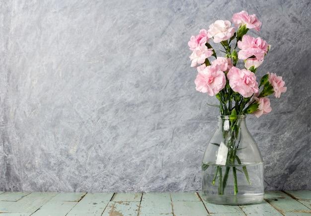 古い木の上に透明なボトルのピンクのカーネーションの花