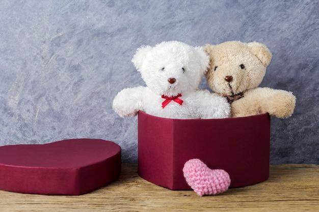 Любовь концепции плюшевого медведя в красном сердце подарочной коробке на деревянный стол для дня святого валентина