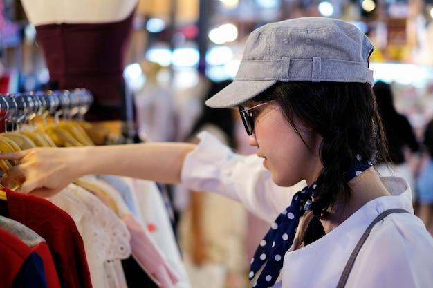 Модная концепция покупки азиатской женщины, выбирающей одежду в магазине