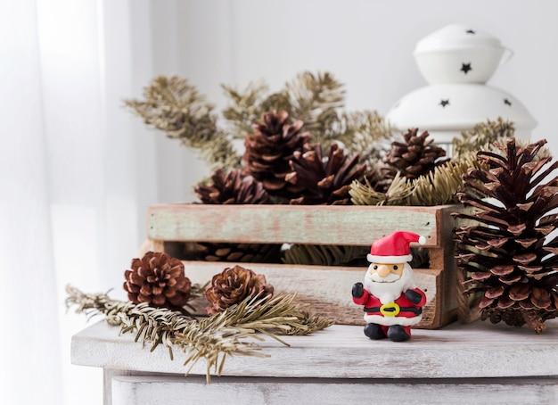 木製のキャビネットのサンタクロースと松のコーンのクリスマスの装飾