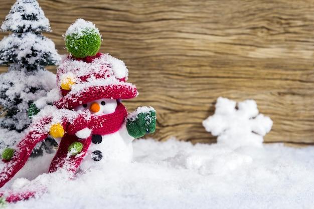 Новогоднее украшение счастливый снеговик, стоящий зимой