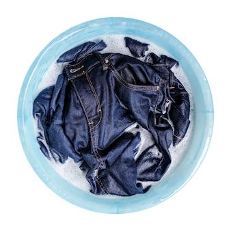 白で隔離されるプラスチック製の洗面器の液体洗剤とブルージーンズ