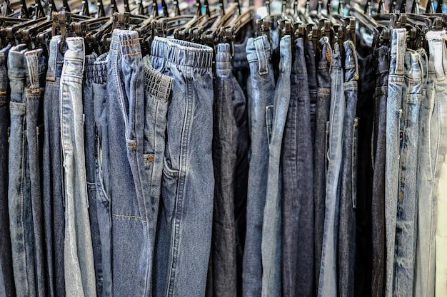 Ряд повешенных синих джинсовых штанов в магазине