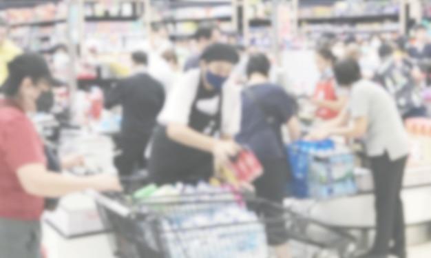 スーパーマーケットで食品を購入する人々の抽象的な背景をぼかした写真