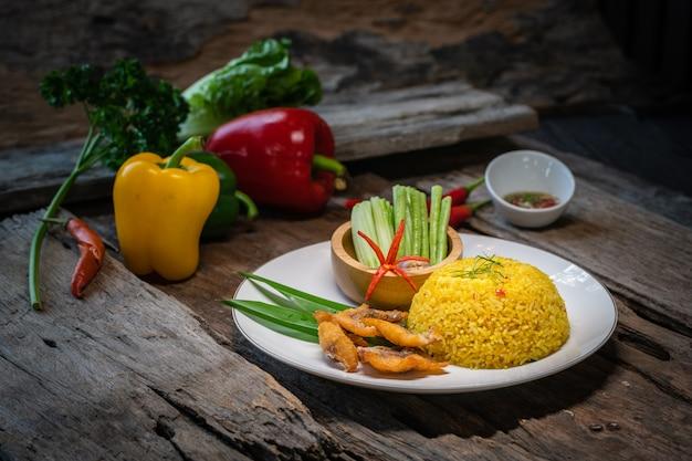 Жареный рис с жареной рыбой на деревянном столе