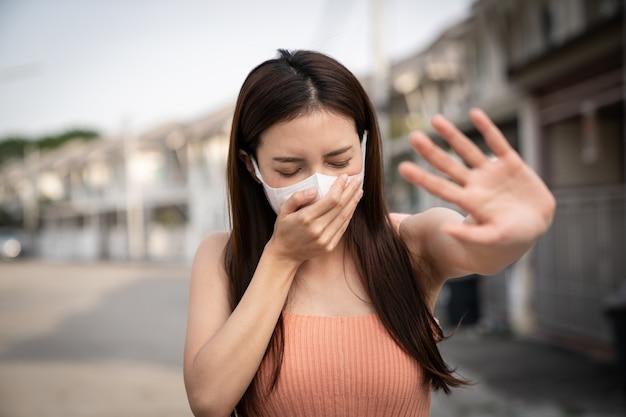 Женщина чувствует себя больной, кашляет или чихает. держит руку перед ней, знак, чтобы остановить. она носит защитную маску.