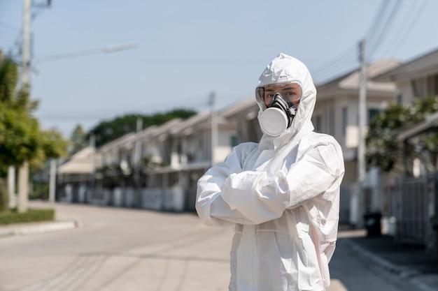 バイオハザード化学防護服とマスクの手袋を着用している女性。彼女は不幸な顔で腕を組んだ。