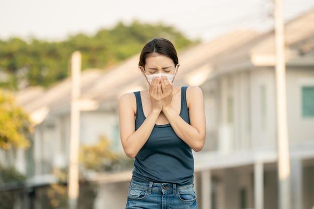 Женщина чувствует себя больной, кашляет или чихает. она носит защитную маску.