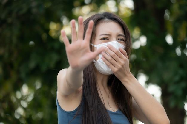 Женщина с несчастным лицом, держит две руки перед ней, знак остановки, знак остановки. она носит защитную маску.