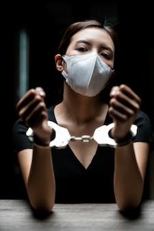 Наручники на заключенного, женщины-заключенные были наручниками в темной тюрьме.