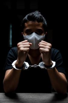 Наручники на заключенного, заключенные-мужчины были наручниками в темной тюрьме.