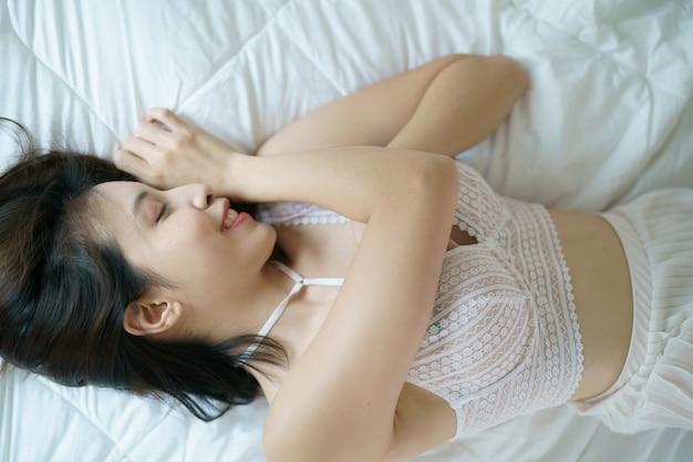 セクシーな女性が、ベッドでポーズします。