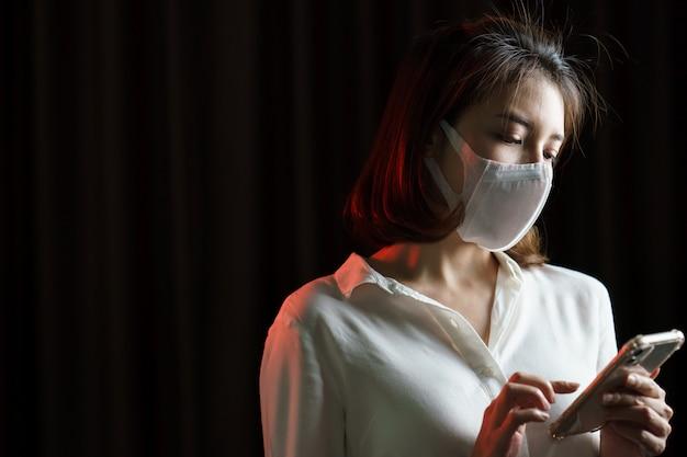Женщина носит защитную маску и использует смартфон