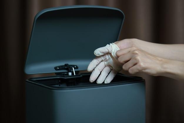 使用済みの汚れた手術用手袋をゴミ箱に置く手。マスクはゴミやほこりやコロナウイルスを保護します。
