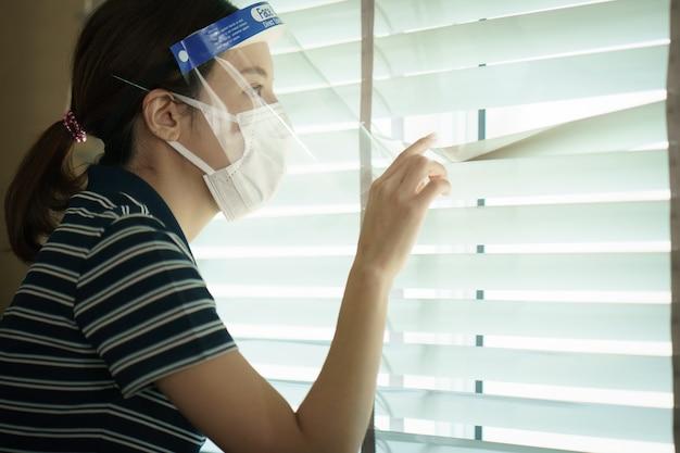 窓のブラインドを通して見る保護医療スクリーンまたはプラスチック製の顔面シールドを身に着けている女性。ウイルス防止