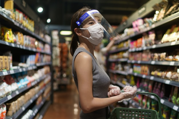手袋、顔面シールド、マスクを身に着けている女性。コロナウイルスの流行中のパニックショッピング。
