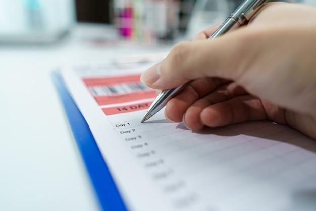 血液検査に関するレポート情報を書く科学者。コロナウイルス検査プロセス。