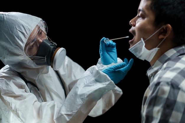 Женщина-врач в защитных костюмах с мазком из носа для проверки на возможную коронавирусную инфекцию