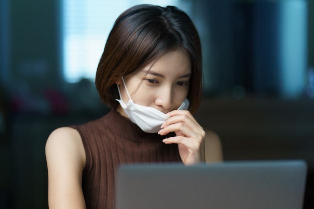 コロナウイルスの発生中に自宅で作業している保護マスクを身に着けている検疫の女性