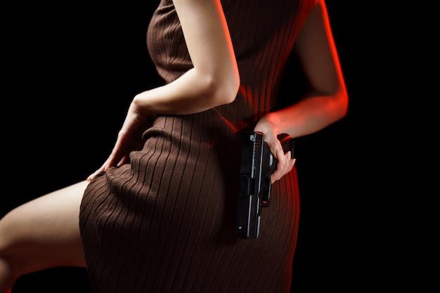 Женщина прячет пистолет за спиной