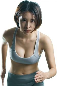 Молодая женщина в серой спортивной одежде дома, делать бег