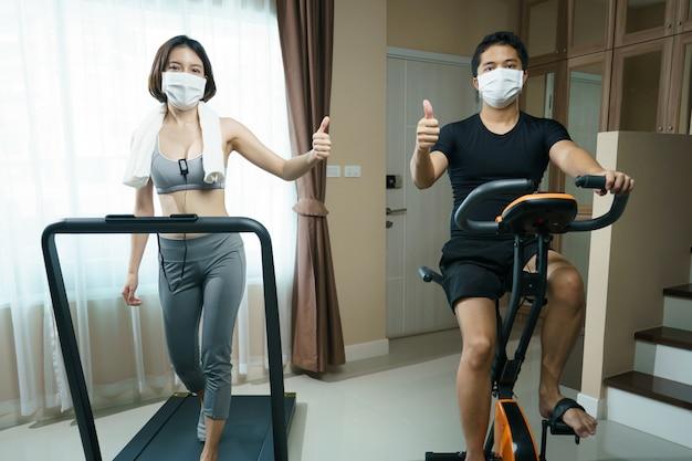 自宅でのエクササイズ:自転車に乗る男性のエクササイズまたは屋内サイクリング、およびマスク付きのトレッドミルで走っている女性:コロナウイルスのパンデミック時のヘルスケア。