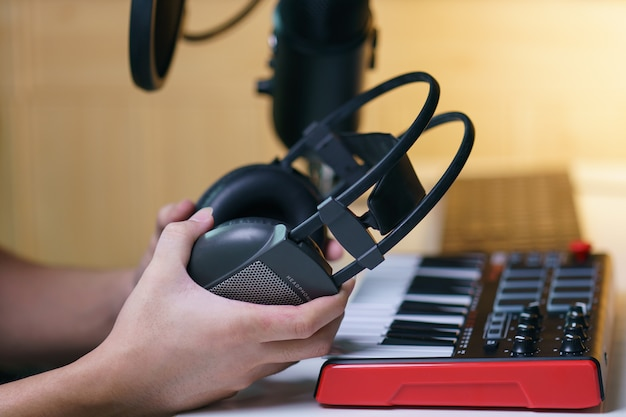 サウンドミキシングコンソールボードの近くのイヤホンを持っている手。音楽スタジオのための機器。