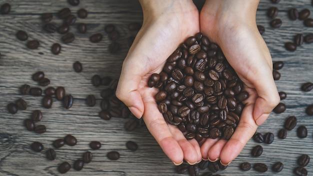 ローストコーヒー豆、クローズアップを保持している女性の手
