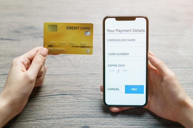 モバイル決済。スマートフォンとクレジットカードを使用してオンラインショッピングの手。