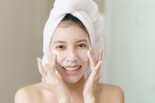 女性は、泡立つクレンザー、清潔で健康な皮膚を適用します。