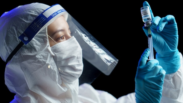 予防、予防接種、コロナウイルス感染の治療のためのワクチンと注射器の注射で防護服を着た女性。