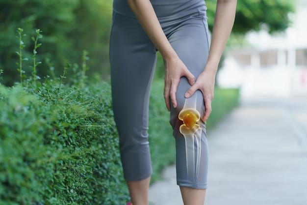 女性は膝に手を握り、膝の痛みは赤で強調され、医学、マッサージのコンセプトです。