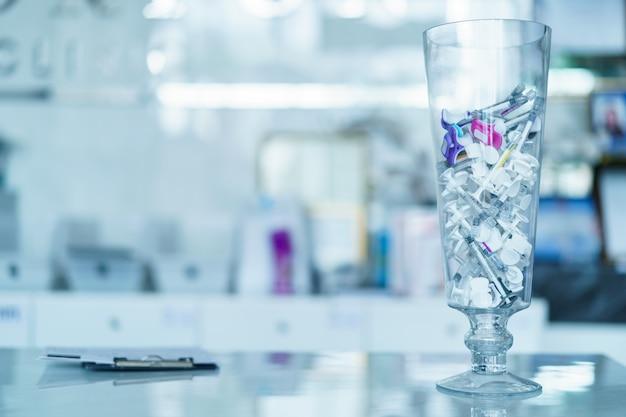 Группа пластиковых шприцев для наполнения инъекций на стеклянной вазе. игла наполнителя.