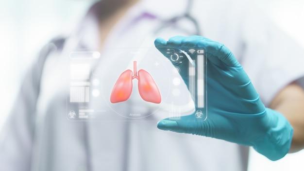 医師の手は、呼吸器症候群(肺)、検査、およびコロナウイルス感染のスクリーニングを示す透明なタブレットディスプレイを持っています。