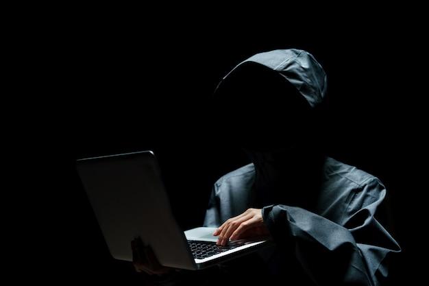 黒い背景にフードで目に見えない男の肖像画。ラップトップを持つハッカー。