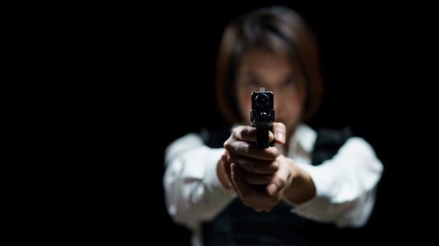 Женщина, носящая пуленепробиваемый жилет, стреляет с оружием в цель в закрытом оружейном диапазоне.