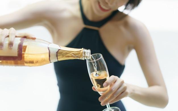 Женщина в черном купальнике наливает игристое вино в бокал.