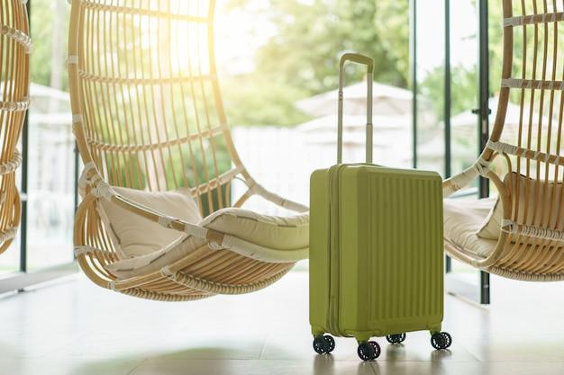 籐製の吊り椅子が付いている緑の荷物、焦点の前の荷物