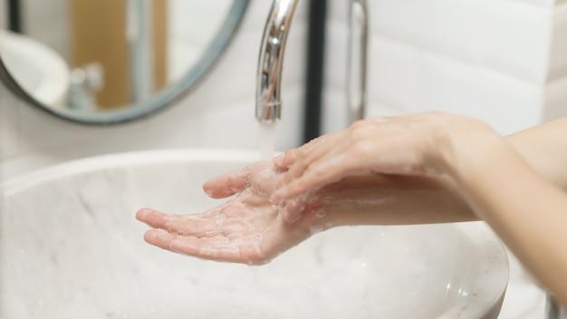 彼女の手を洗う女性、指を集中