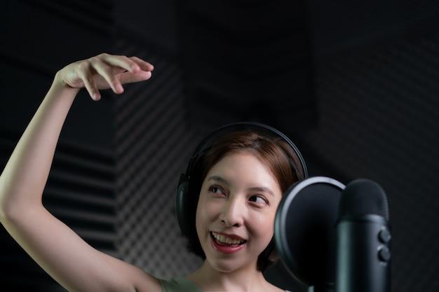 スタジオで歌や物語を録音する女性