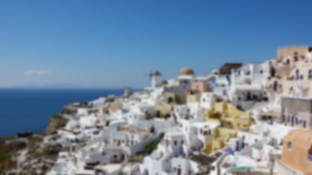 Размытые архитектуры с ветряными мельницами на склоне холма в деревне ия на острове санторини, греция средиземное море.