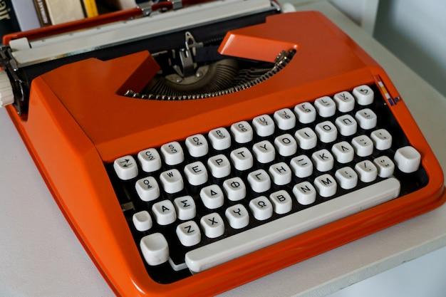 白いテーブルにギリシャ語のアルファベットの赤いヴィンテージタイプライターマシン。