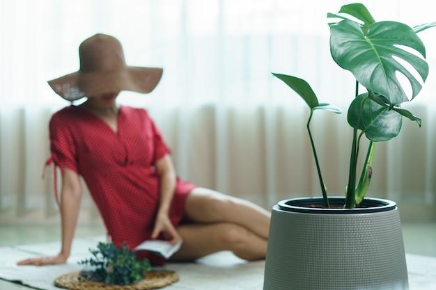 緑の植物の近くの家に座っている本を読んで赤いドレスと帽子の女性。