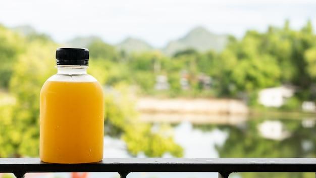 健康的なオレンジジュースのデトックス。手と緑の自然の背景に新鮮なオレンジ色のボトルのクローズアップ。