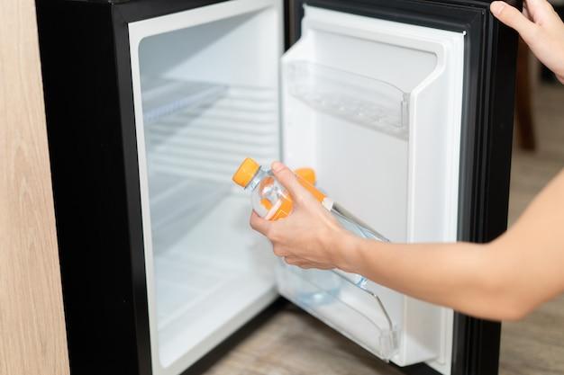 冷蔵庫から水のボトルを取る女性の手。