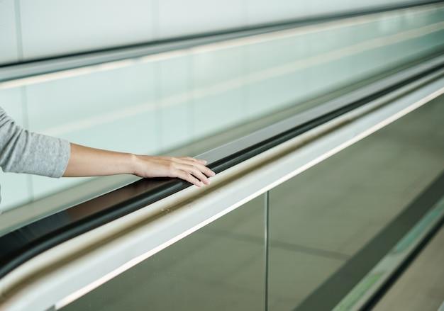 エスカレーターを上がるときに手すりを持っている女性